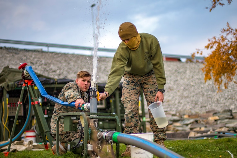 Two Marines release air from a hose.