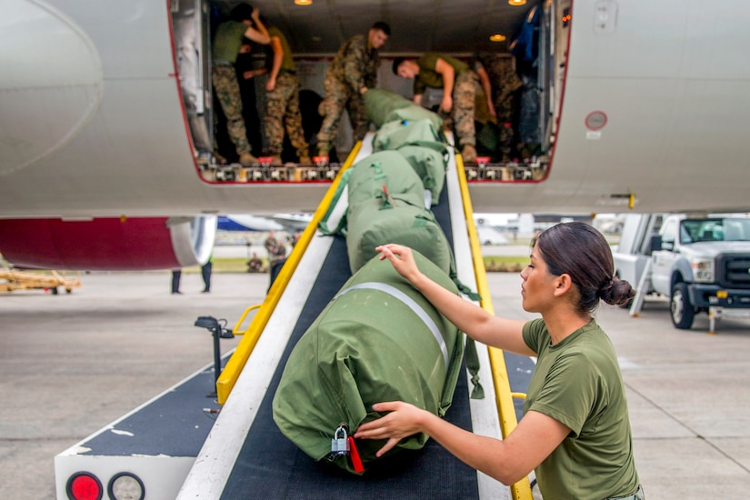 Marines load bags onto an aircraft.