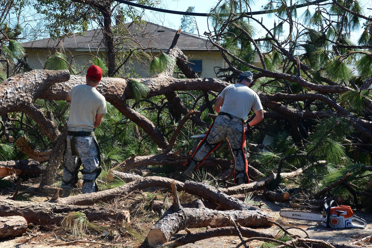 Airmen use chain saws to clear fallen trees in neighborhoods near the 10 Mile Road area in Panama City.