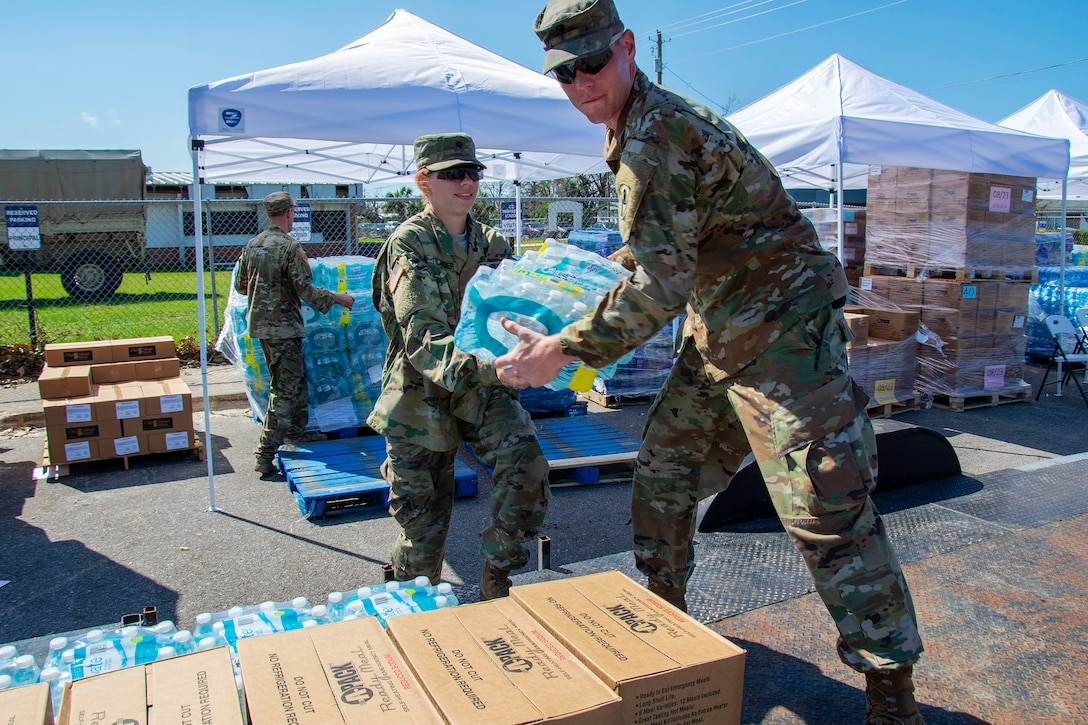 Soldiers distribute water and supplies to residents in need following Hurricane Michael.