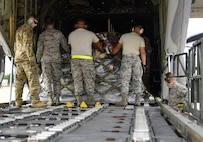 U.S. Air Force Airmen from the 733rd Logistics Readiness Squadron small air terminal assist the 71st Rescue Squadron loadmasters with the gear and supplies being sent to Tyndall Air Force Base, Florida, onto a HC-130J Combat King II at  Joint Base Langley-Eustis, Virginia, Oct. 17, 2018. The HC-130J is from the 71st Rescue Squadron at Moody Air Force Base, Georgia. (U.S. Air Force photo by Staff Sgt. Carlin Leslie/Released)