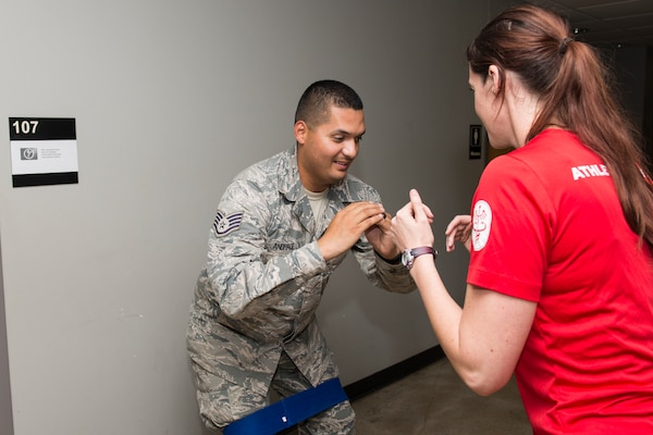 Jacquelyn Hale, a 343rd Training Squadron athletic trainer, walks a 343rd TRS instructor through physical training exercises