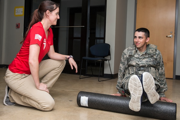 Jacquelyn Hale, a 343rd Training Squadron athletic trainer, walks a 343rd TRS trainee through physical training exercises