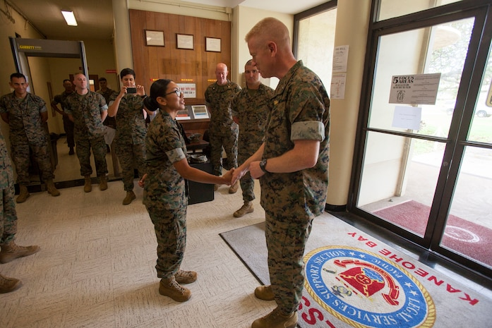 U.S. Marine Corps Brig. Gen. Paul J. Rock Jr., commanding general, Marine Corps Installations Pacific (MCIPAC), shakes hands with and gives Cpl. Esmeralda Guzmananaya, Legal Services Support Team Marine with Headquarters Battalion, Marine Corps Base Hawaii (MCBH), a MCIPAC challenge coin at the legal building during his visit to MCBH, Oct. 15, 2018. From being MCIPAC's meritorious sergeant nominee to Hawaii's USO service member of the year, Rock recognized four Marines then sat down and enjoyed chow with them and along other MCBH Marines. (U.S. Marine Corps photo by Sgt. Zachary Orr)