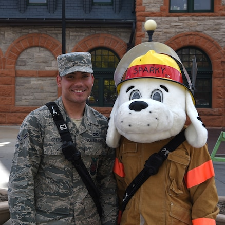 Airman 1st Class Anthony Ebersole stands with Sparky at the Fire Prevention Week Open House on Oct. 13, 2018 at the Depot Plaza, Cheyenne, Wyo. These two individuals represented F. E. Warren Air Force Base and passed on vital safety information to the patrons attending the event. TIP: Test alarms at least once a month by pressing the test button.
