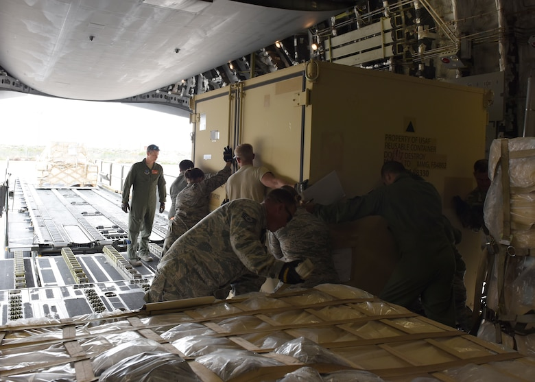 Airmen from the 49th Logistics Readiness Squadron and the 635th Materiel Maintenance Group lock equipment into place, Oct. 15, 2018, on a C-17 Globemaster III, assisted to the Memphis Air National Guard, on the flightline at Holloman Air Force Base, N.M. The 49th LRS supported Airmen from the 635th MMG in a recent operation to send essential supplies to Tyndall Air Force Base, Fla. (U.S. Air Force photo by Airman Autumn Vogt)