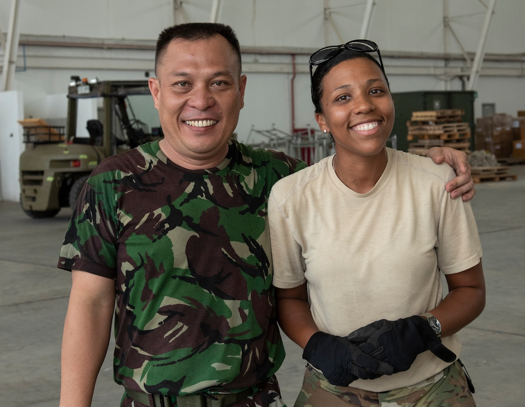 U.S. Air Force Master Sgt. Sarah Kramarius, 36th Mobility Response Squadron assessment team chief, at Andersen Air Force Base, Guam, poses with a photo with an Indonesian military member in Balikpapan, Indonesia Oct. 12, 2018. Members from the 36th Contingency Response Group worked and train alongside host nation partners to ensure supplies were delivered immediately to thousands of Indonesians affected by a recent tsunami and earthquake (U.S. Air Force photo by Master Sgt. JT May III)