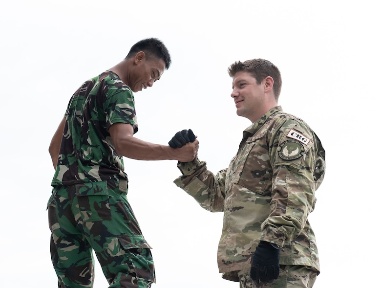 U.S. Air Force Tech. Sgt. Chad Davis, 36th Mobility Response Squadron command and control operator, at Andersen Air Force Base, Guam shakes hand with an Indonesian military member after assembling a U.S. Agency for International Development (USAID) pallet in Balikpapan, Indonesia Oct. 12, 2018. USAID is airlifting    over 2,210 rolls of heavy-duty plastic sheeting to provide emergency shelter for 110,500 people in Indonesia and is working with its partners to provide emergency shelter kits, blankets, hygiene kits, solar-powered lamps, other critical relief supplies. USAID has also made it a priority to ensure children have safe spaces to play to cope with the disaster. (U.S. Air Force photo by Master Sgt. JT May III)