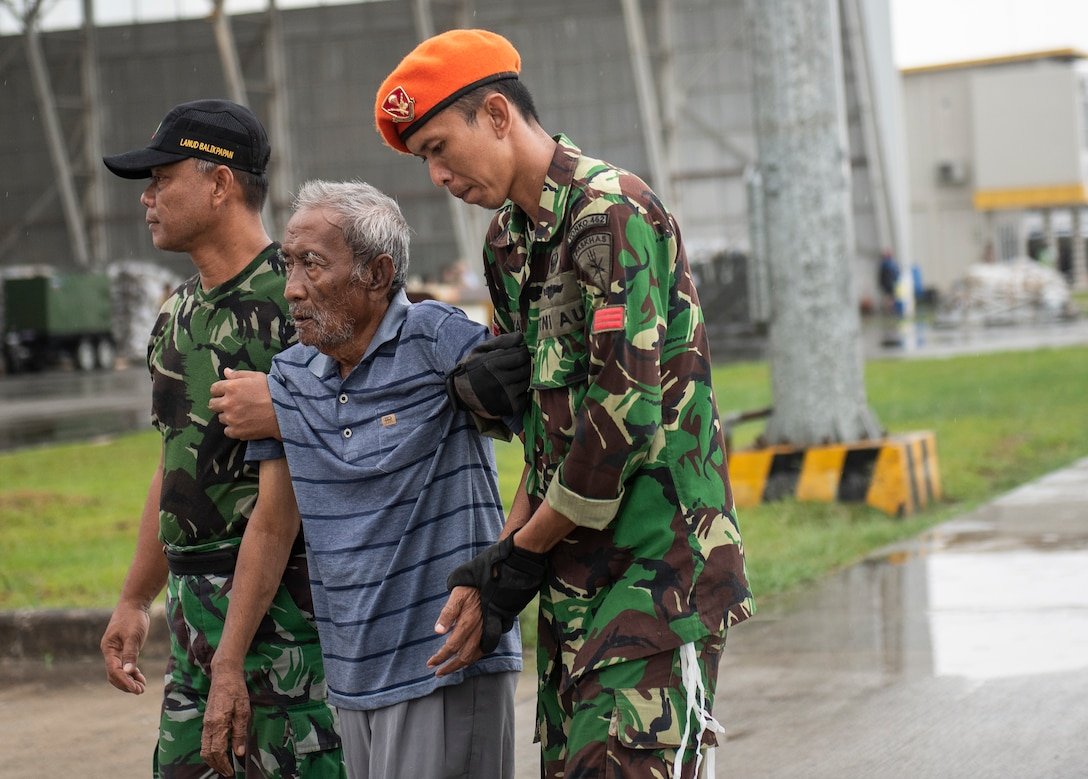 Two Indonesian soldiers assist an injured Indonesian man after arriving to the airport in Balikpapan, Indonesia Oct. 10, 2018. The airport is used a staging ground for humanitarian supplies and an evacuation point for displaced people affected by a recent tsunami and earthquake. (U.S. Air Force photo by Master Sgt. JT May II)