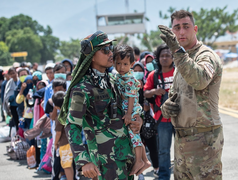 U.S. Air Force Staff Sgt. Michael Mendes, 36th Mobility Response Squadron loadmaster, assists an Indonesian soldier and child with instructions before boarding a Republic of Singapore Air Force C-130 in Palu, Indonesia Oct. 10, 2018, The Indonesian Government and U.S. Agency for International Development are working alongside 15 countries agencies and foreign militaries ensuring supplies, airlift, shelter and medical support reach those affected. (U.S. Air Force photo by Master Sgt. JT May III)