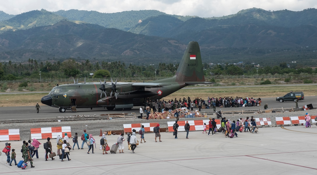 Hundreds of displaced people from Indonesia prepare to board an Indonesian C-130 aircraft in Palu, Indonesia Oct. 10, 2018. Thousands were displaced after a 7.5 magnitude earthquake and tsunami struck Indonesia's Sulawesi Island Sept. 28, 2018. The Indonesian Government and U.S. Agency for International Development are working alongside eight countries agencies and foreign militaries ensuring supplies, airlift, shelter and medical support reach those affected. (U.S. Air Force photo by Master Sgt. JT May III)