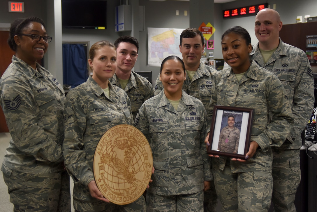 Seven Airmen wearing the Airmen Battle Uniform hold up a command post sign made of wood and a photo of an Airman down range.