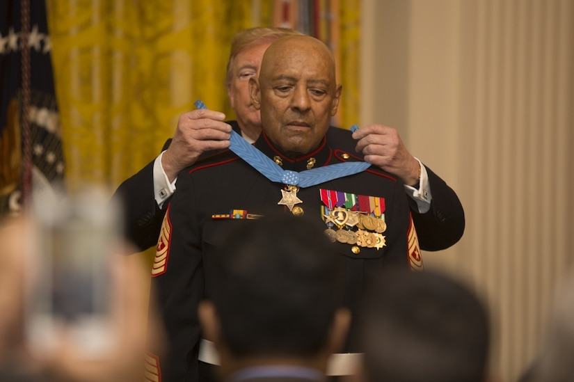 President Donald J. Trump places a medal around the neck of a Marine.