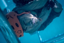 A Marine with the 11th Marine Expeditionary Unit is flipped upside-down in a shallow water egress trainer at Camp Pendleton, California, Oct. 12, 2018. The SWET prepares Marines to train in the Modular Amphibious Egress Trainer, a simulated sinking aircraft, and is a requirement for all Marines that will deploy with the 11th MEU.