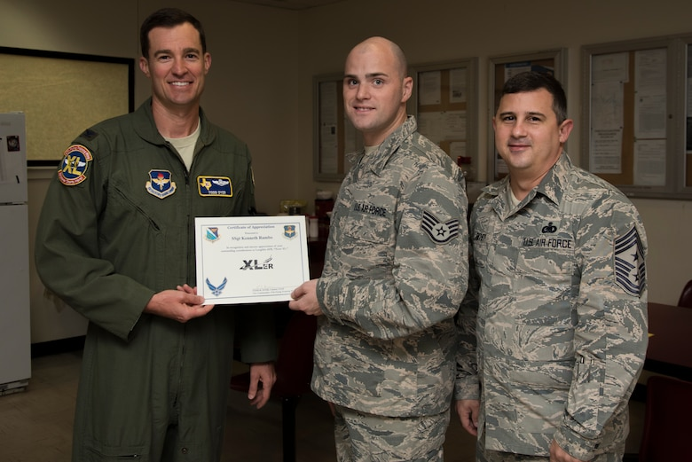 """Staff Sgt. Kenneth Rambo, 47th Flying Training Wing egress systems craftsman, was chosen by wing leadership to be the """"XLer"""" of the week, for the week of Oct. 8, 2018, at Laughlin Air Force Base, Texas. The """"XLer"""" award, presented by Col. Todd Dyer, 47th Flying Training Wing vice commander, is given to those who consistently make outstanding contributions to their unit and the Laughlin mission. (U.S. Air Force photo by Airman 1st Class Marco A. Gomez)"""