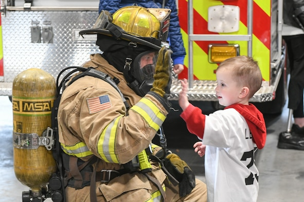 Clark Lenehan high-fives Duncan Hutchinson, a firefighter with 775th Civil Engineering Squadron, during a visit to the fire department Oct. 11, 2018, at Hill Air Force Base, Utah. The visit was part of a 75th Air Base Wing-hosted base tour for Make-A-Wish Utah children and their families. (U.S. Air Force photo by Cynthia Griggs)