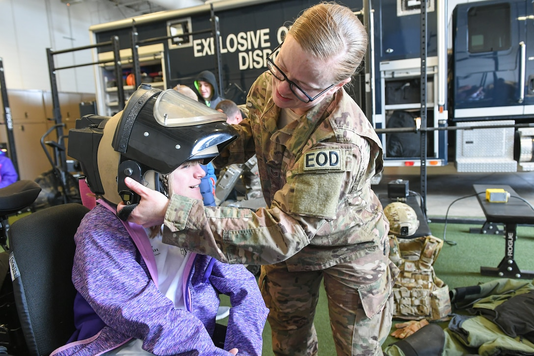 Tech. Sgt. Jessica Johnson, 775th Explosive Ordinance Disposal Flight, puts a helmet on Breanna Heim during a visit to EOD Oct. 11, 2018, at Hill Air Force Base, Utah. The visit was part of a 75th Air Base Wing-hosted base tour for Make-A-Wish Utah children and their families. (U.S. Air Force photo by Cynthia Griggs)
