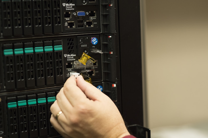 Photo of hand inserting PadJack device into an Ethernet port on a server.