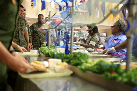 Capt. Veronica Abosi and mess hall workers serve food to Marines and Sailors during the Navy birthday celebration aboard Marine Corps Air Station Beaufort, Oct. 17. Abosi is a supply officer with Headquarters and Headquarters Squadron aboard the air station.
