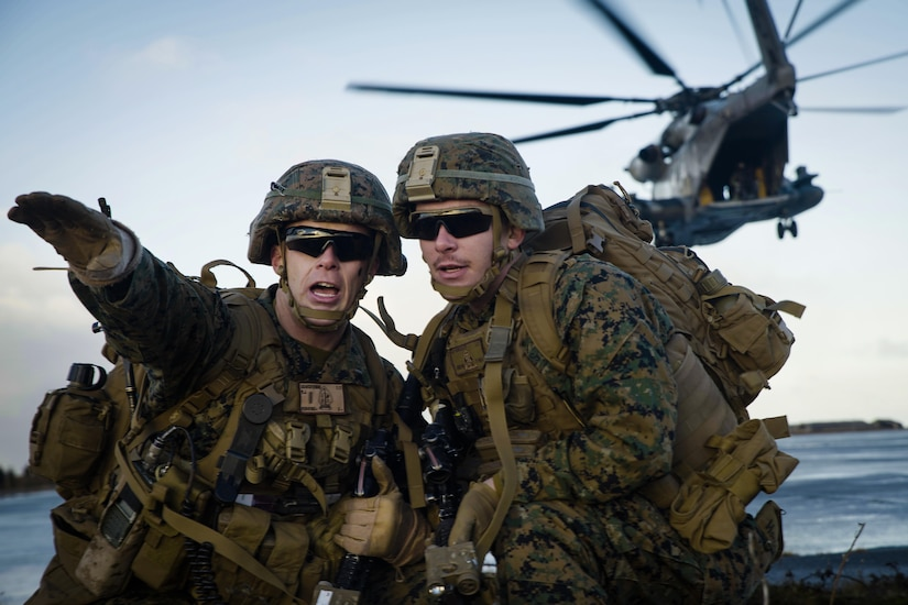 A Marine gestures while giving directions to a team member as a helicopter flies away over water.