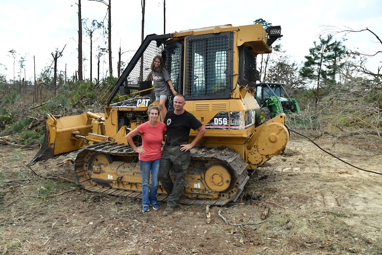 Kelly Bunting, U.S. Army Corps of Engineers Mobile District Park Ranger at the Lake Seminole Project, her husband Nate, and her daughter Norah, pose in front of their bulldozer in back of their house on Oct. 16, 2018 in Sneads, Fla. The Buntings survived Hurricane Michael by riding out the Category 4 storm in their bulldozer.