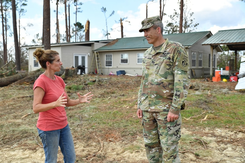 Kelly Bunting, U.S. Army Corps Engineers Park Ranger at the Lake Seminole Project, describes how her family survived Hurricane Michael to Col. Sebastien P. Joly during his visit to the family home on Oct. 16, 2018, in Sneads, Fla. The Buntings survived the Category 4 storm by riding out inside of a bulldozer.