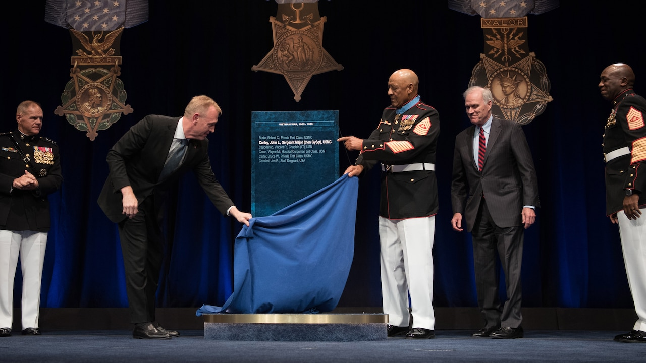 Deputy Defense Secretary Patrick M. Shanahan and Medal of Honor recipient retired Marine Corps Sgt. Maj. John L. Canley remove the curtain from Canley's Hall of Heroes plaque.