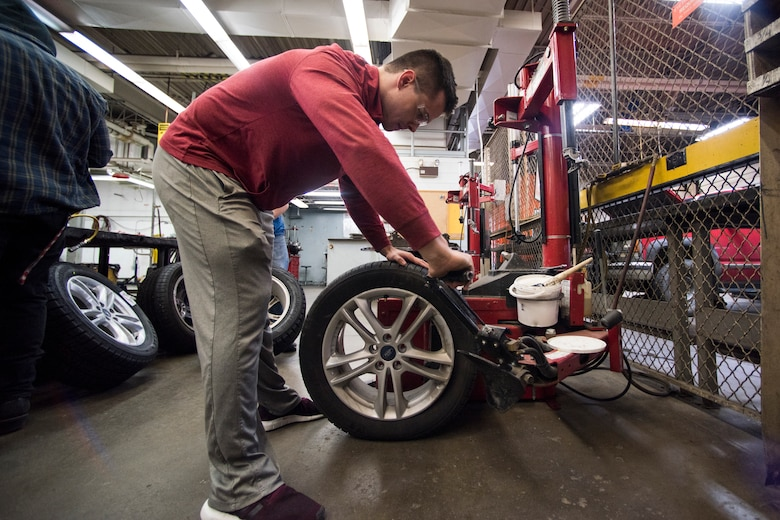 Bryce Ward, a University of Alaska Anchorage ROTC cadet, removes a summer tire from the rim at the Auto Skills Center at Joint Base Elmendorf-Richardson, Alaska, Oct. 17, 2018. The Auto Skills Center is home to a full array of equipment, tools and knowledgeable staff for do-it-yourself maintenance and repair to personal vehicles.