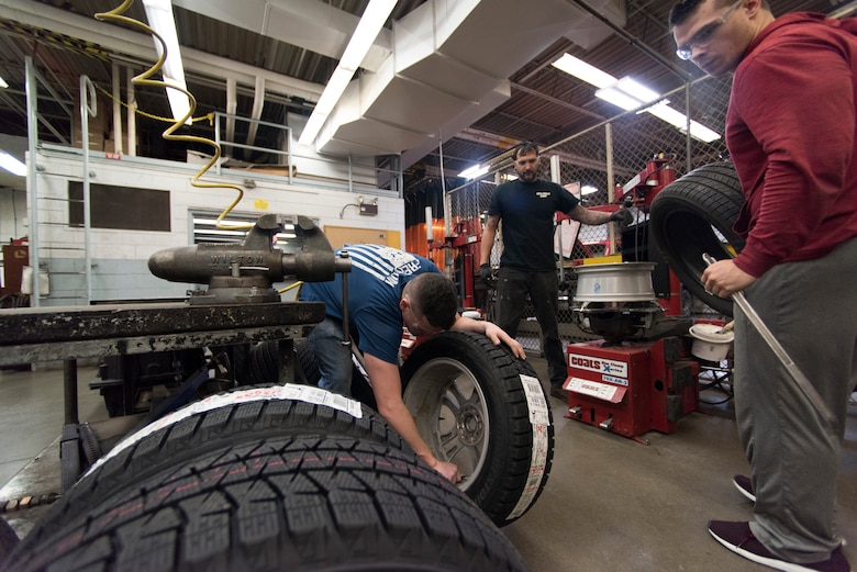 Benjamin Mock, left, a University of Alaska Anchorage ROTC cadet, sets a newly installed winter tire on the ground as Bryce Ward, right, UAA ROTC cadet, removes a summer tire at the Auto Skills Center at Joint Base Elmendorf-Richardson, Alaska, Oct. 17, 2018. The Auto Skills Center is home to a full array of equipment, tools and knowledgeable staff for do-it-yourself maintenance and repair to personal vehicles.