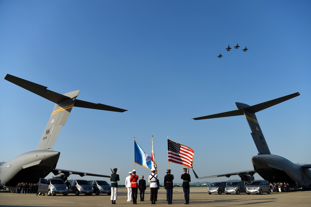 The United Nations Command Honor Guard prepares to transfer caskets of remains onto waiting C-17 Globemaster IIIs as members of the 36th Fighter Squadron perform a missing man flyover at Osan Air Base, Republic of Korea, Aug. 1, 2018. Two C-17s left Osan AB for Joint Base Pearl Harbor-Hickam, Hawaii, where members of the Defense POW/MIA Accounting Agency will attempt to identify the remains of the fallen heroes. The UNC repatriated 55 cases of remains from the Democratic People's Republic of Korea. (U.S. Air Force photo by Senior Airman Kelsey Tucker)