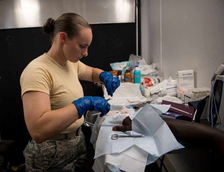 U.S. Air Force Staff Sgt. Jessica Ewens, a 96th Aeromedical Squadron independent duty medical technician out of Eglin Air Force Base, Florida, provides medical care to a patient inside a mobile medical clinic at Tyndall Air Force Base, Florida, Oct. 17, 2018. Support personnel from Tyndall and other bases were on location to support Airmen returning to their homes to assess damage and collect personal belongings. (U.S. Air Force photo by A1C Kelly Walker)