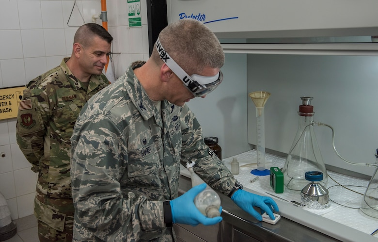 39th Air Base Wing commander, and  command chief participate in a fuel inspection with lab technicians