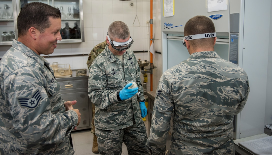 Three Logistics Airmen preform tests on a aircraft fuel system icing inhibitor.