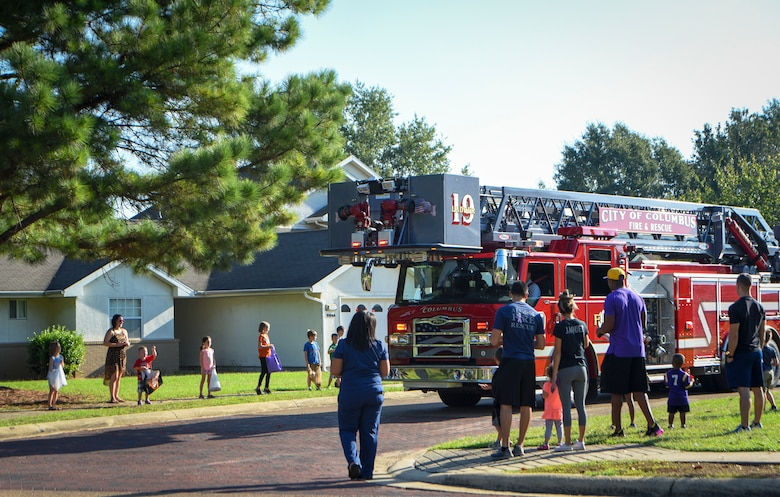 "Residents of Magnolia Housing on Columbus Air Force Base, Mississippi, watch fire trucks pass by and toss out candy during a parade Oct. 6, 2018. The parade kicked off Fire Prevention Week for Columbus AFB and this year's theme was ""Be aware. Fire can happen anywhere."" (U.S. Air Force photo by Tech. Sgt. Christopher Gross)"