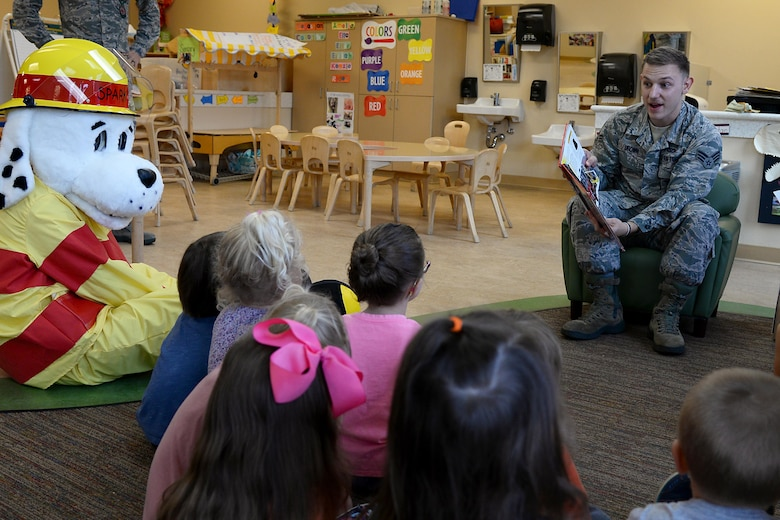 Senior Airman Dylan Brown, 14th Civil Engineer Squadron Firefighter, reads to the fire prevention mascot Sparky and children at the Child Development Center Oct. 10, 2018. Fire Prevention week was held from Oct. 6-12 here to remind Team BLAZE about the importance of fire prevention. (U.S. Air Force photo by Airman 1st Class Keith Holcomb)