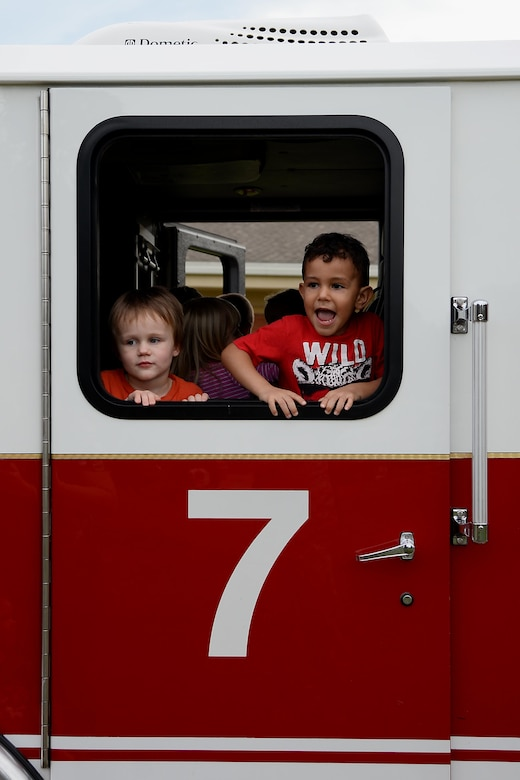 Ryder Lee and Jeremiah Samuels look out of a 14th Civil Engineer Squadron fire truck Oct. 10, 2018, outside the Child Development Center of Columbus Air Force Base, Mississippi. The 14th Civil Engineer Squadron firefighters from Station 2 hosted engaging and hands-on events to teach children and remind individuals how to better prevent house and work fires. (U.S. Air Force photo by Airman 1st Class Keith Holcomb)