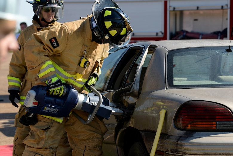 Airman 1st Class Blake Harwell and Senior Airman Jacob Sanford, 14th Civil Engineer firefighters, demonstrate during an open house their ability to rescue an individual from a vehicle Oct. 6, 2018, on Columbus Air Force Base, Mississippi. The 14th CES firefighters respond to aircraft and facility emergencies within minutes and have the ability to control, contain and stop numerous types of emergencies from escalation. (U.S. Air Force photo by Airman Hannah Bean)