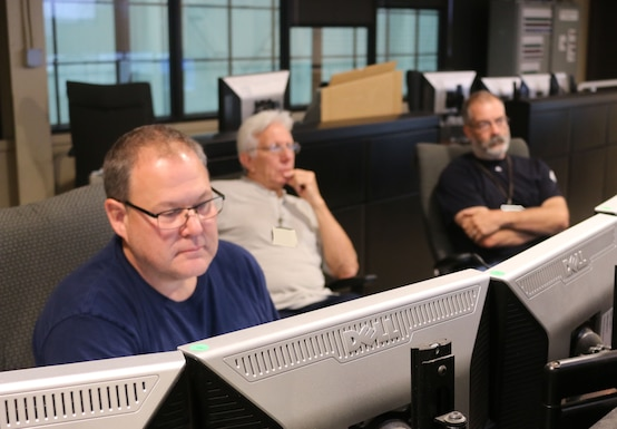 AEDC electricians Eddie Lee, left, Chuck Kurtsinger, center, and Carlos Bussche, right, check the plant control valves from a control room in the von Kármán Facility at Arnold Air Force Base. (U.S. Air Force photo by Bradley Hicks) (This image was manipulated by obscuring badges for security purposes)