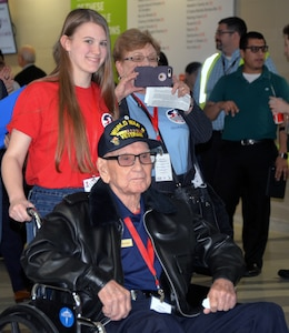 A World War II veteran, along with his high school escort, enjoy the reception as they arrive for a sendoff ceremony at the San Antonio International Airport Oct. 17, which saw 40 WWII veterans take off for a trip to New Orleans to visit the National World War II Museum. The Soaring Valor program, sponsored by the Gary Sinise Foundation, helped send the veterans and 40 high school Student companions from Dallas, to the museum.