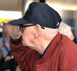 A World War II veteran renders a salute during the singing of the National Anthem at the conclusion of a sendoff ceremony at the San Antonio International Airport Oct. 17 which saw 40 WWII veterans take off for a trip to New Orleans to visit the National World War II Museum. The Soaring Valor program, sponsored by the Gary Sinise Foundation, helped send the veterans and 40 high school Student companions from Dallas, to the museum.