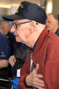 A World War II veteran holds his hand over his heart during the Pledge of Allegiance at the conclusion of a sendoff ceremony at the San Antonio International Airport Oct. 17 which saw 40 WWII veterans take off for a trip to New Orleans to visit the National World War II Museum. The Soaring Valor program, sponsored by the Gary Sinise Foundation, helped send the veterans and 40 high school Student companions from Dallas, to the museum.