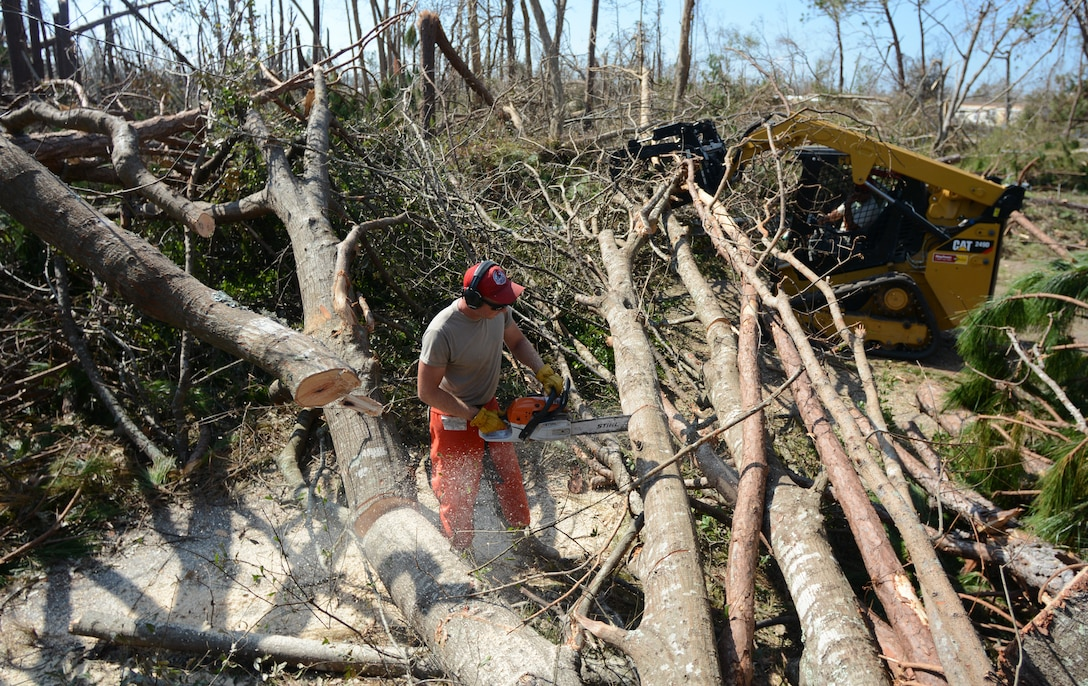 Staff Sgt. Christopher Lybrand, structures craftsman with the 202nd RED HORSE Squadron, trims a tree trunk into smaller logs Oct. 16, 2018, in Panama City, Fla. The RED HORSE team used chainsaws, skid steers and back hoes to unblock caused by damage from Hurricane Michael. (U.S. Air Force photo Courtesy Photo)