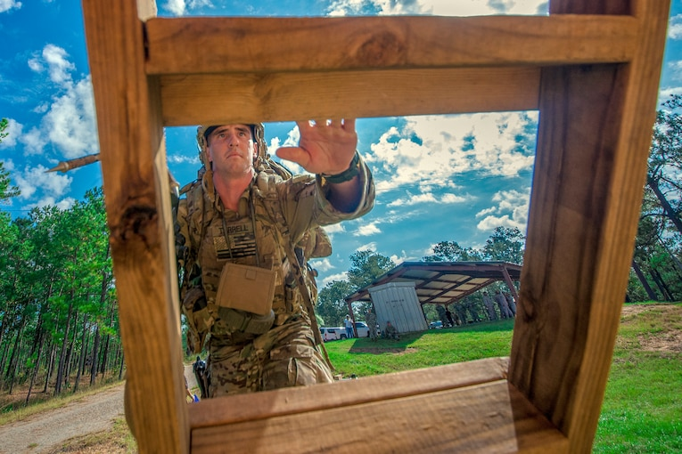 A soldier climbs a wooden obstacle.