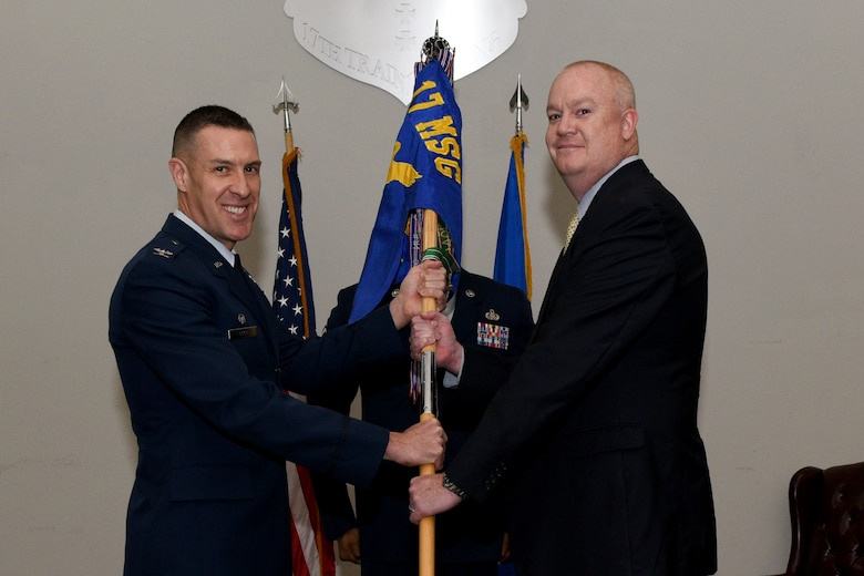 U.S. Air Force Col. Jason Beck, 17th Mission Support Group commander, gives the guideon to 17th Force Support Squadron incoming Director William Dowell, during the 17th FSS assumption of leadership at the Event Center on Goodfellow Air Force Base, Texas, October 19, 2018. The assumption of leadership ceremony is a time honored military tradition that signifies the orderly transfer of authority. (U.S. Air Force photo by Senior Airman Randall Moose/Released)