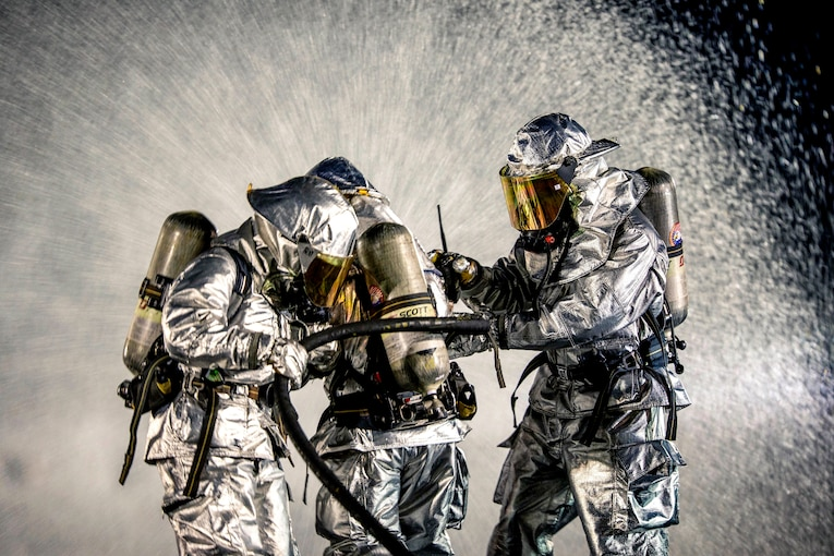 Three firefighters in silver protective gear hold a hose spraying water, which fills the frame.