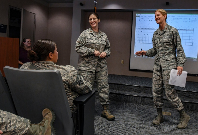 Air Force Safety Center Human Factor Workshop instructors, Maj. Heather Tevebaugh, left, and Maj. Nancy Delaney, brief students during their course at Joint Base Langley-Eustis, Virginia, Oct. 10, 2018. Delaney and Tevebaugh are both subject-matter experts from their career fields who travel around the world to teach Airmen about the human factors involved in accident investigation boards and occupational safety. (U.S. Air Force photo by Tech. Sgt. Nick Wilson)
