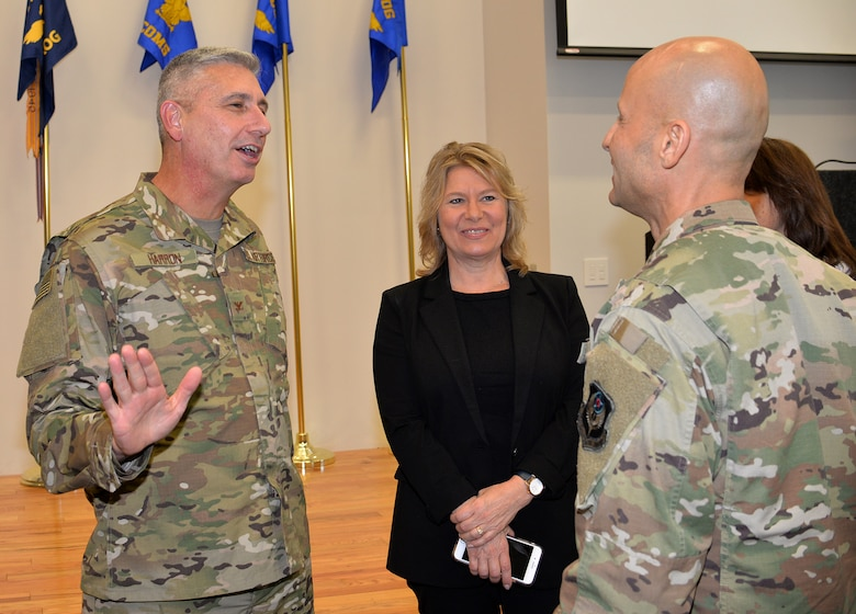 """Col. Scott Harron (left), 193rd Air Operations Group commander, and his wife, Kelly, speak to Col. Terrence Koudelka, 193rd Special Operations Wing commander, following Harron's assumption of command ceremony at the AOG Oct. 18. Before taking on the role as AOG commander, Harron served as the 25th Air Force Inspector General, and as Inspection Team Chief at Air Combat Command headquarters. He also served as commander of the 152nd Air Intelligence Squadron at Hancock Field Air National Guard Base, Mattydale, N.Y. Harron spent 16 years as an enlisted troop before commissioning as an Air Force intelligence officer in September 2000. """"Scott is the absolute perfect person for this position. His intel experience and track record of deployments is nothing short of impressive,"""" Koudelka said. (U.S. Air National Guard photo by 1st Lt. Susan Penning/Released)"""