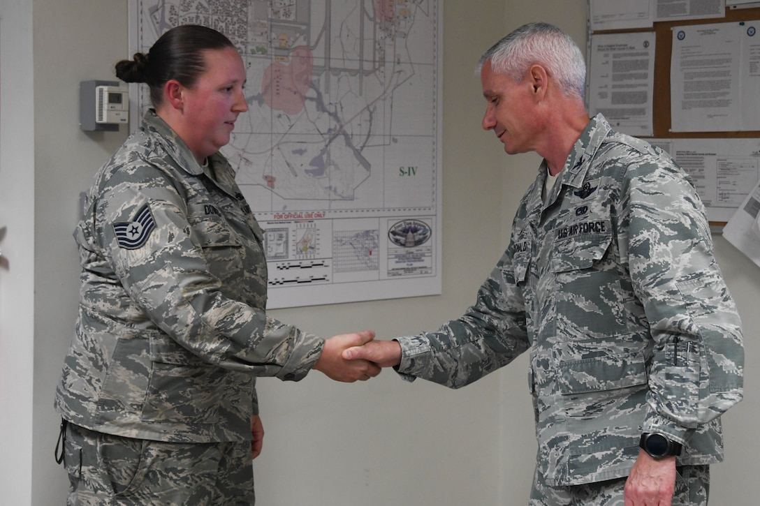 Tech. Sgt. Kelly Downes, a 213th Air Maintenance Squadron phase inspector, is coined by Col. Keith G. MacDonald, 113th Wing Commander, at Andrews Air Force Base for her bravery in saving her neighbor from a house fire, Oct. 17. (U.S. Air National Guard photo by Staff. Sgt. Erica Rodriguez)