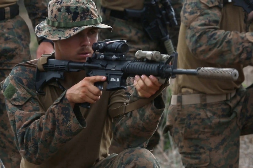 A Marine aims an M-4 carbine during an exercise.