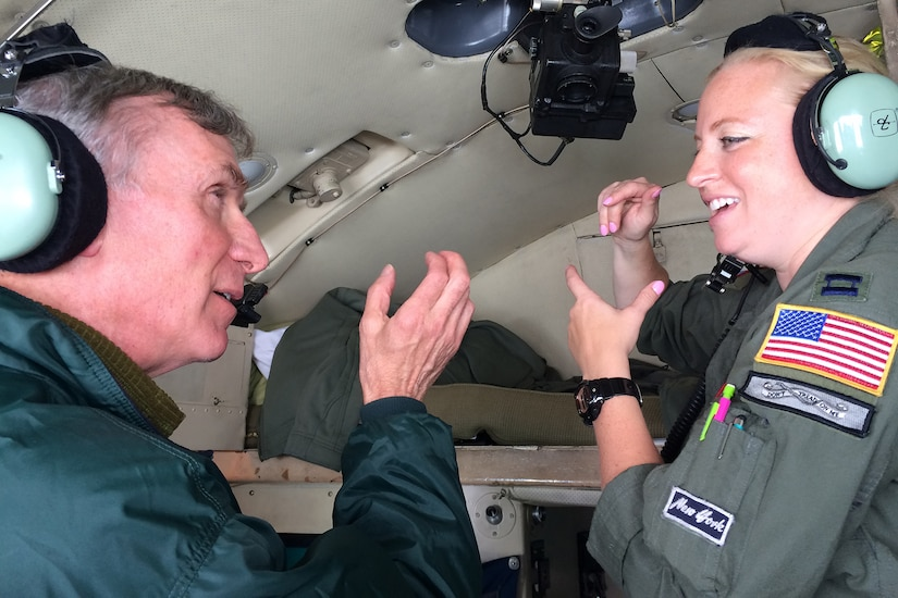 Bill Nye talks with airman on airplane.